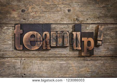 team up, phrase set with vintage letterpress printing blocks on rustic wooden background