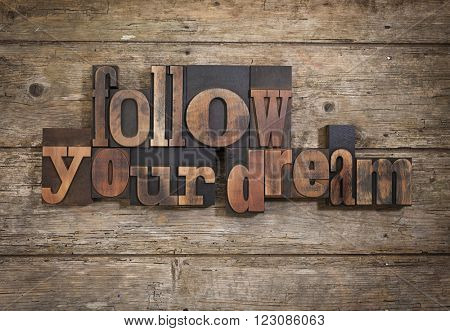 follow your dream, phrase set with vintage letterpress printing blocks on rustic wooden background