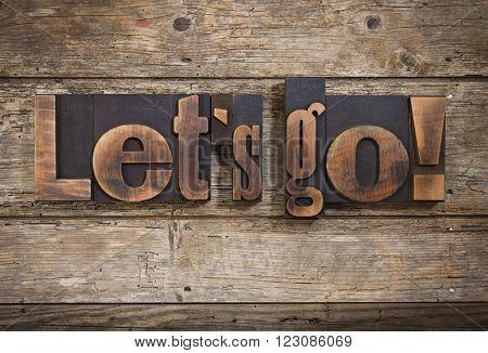 let's go, phrase set with vintage letterpress printing blocks on rustic wooden background