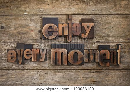 enjoy every moment, phrase set with vintage letterpress printing blocks on rustic wooden background