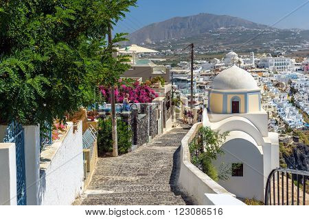 THIRA, SANTORINI, GREECE - AUGUST 24, 2015: Stony road to Thira town among churches and traditional houses on Santorini island, Greece