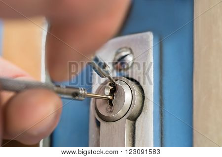 Close-up Of Lockpicker Hand Fixing Door Handle At Home poster