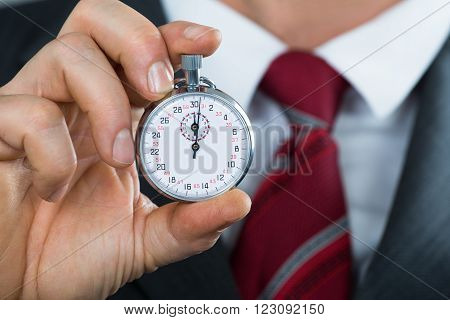Close-up Of Businessman Hand Holding Stop Watch