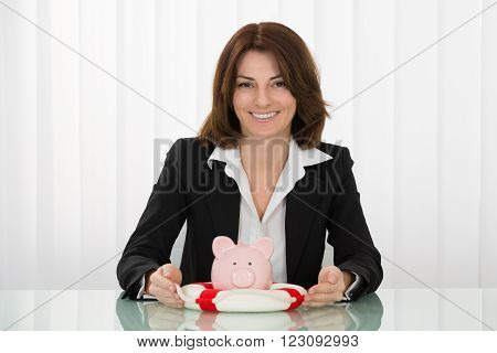 Happy Young Businesswoman Sheltering Piggybank With Lifebelt