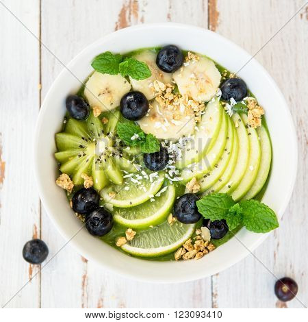 Healthy Green Smoothie in the Bowl from Banana and Spinach with Blueberries Lime Apple Mint Granola Coconut and Kiwi on top Top View