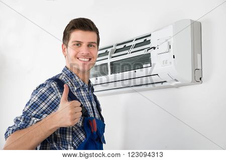 Young Happy Male Technician Gesturing Thumb Up