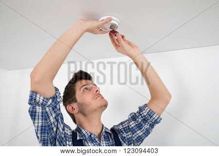Young Male Electrician Repairing Smoke Detector On Wall