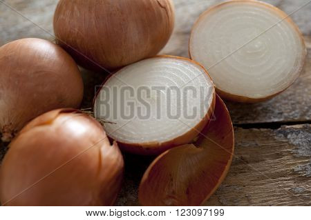 Close up of three whole and one halved fresh spanish onion with papery skin on a rustic wooden surface