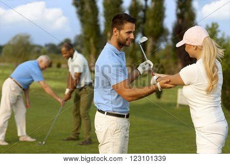 Female golfer learning golfing, male instructor helping.