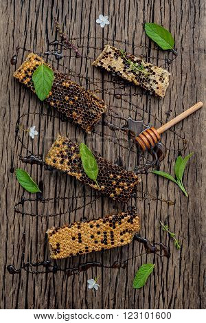 Honeycomb And Honey  With Peppermint ,thyme And Sage Set Up On Dark Wooden Background.