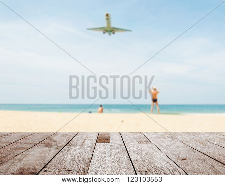 Summer and travel concept Wood table top on blurred blue sea and white sand beach with some people and plane Can be used for display or montage your products