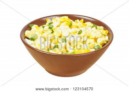 Salad with egggreen onioncheese on brown bowl isolated on white