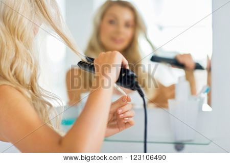 beauty, hairstyle, morning and people concept - close up of young woman with styling iron straightening her hair and looking to mirror at home bathroom