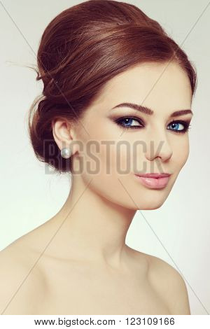 Vintage style portrait of young beautiful woman with stylish hair bun and smoky eyes