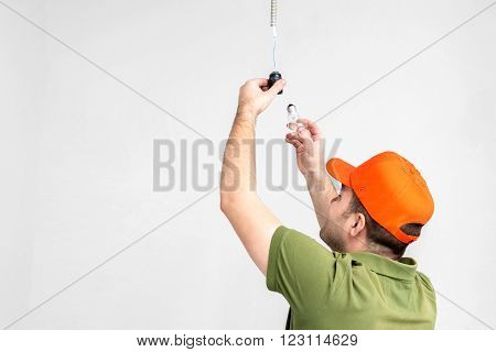 worker man changing light bulb in flat