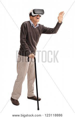 Full length portrait of a senior with a cane experiencing virtual reality through VR headset isolated on white background