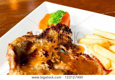 traditional style juicy porkchop with french fried on white plate in restaurant for lunch