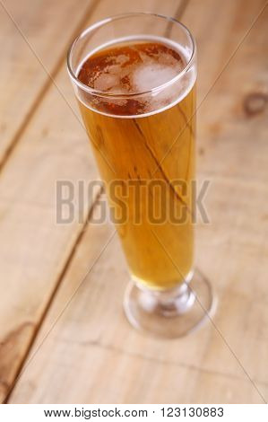 Pilsner vase glass with light beer on a grunge wood background