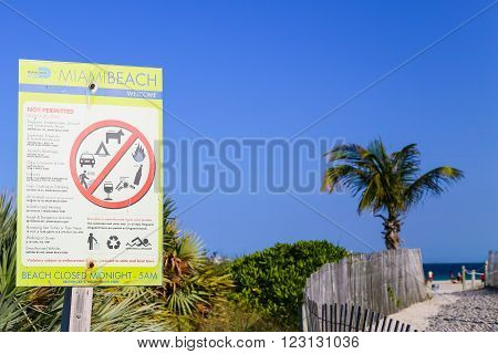 MIAMI BEACH, USA - MAY 9, 2015: A prohibition sign showing not permitted activities on the beach with an entrance to the beach In the backround.