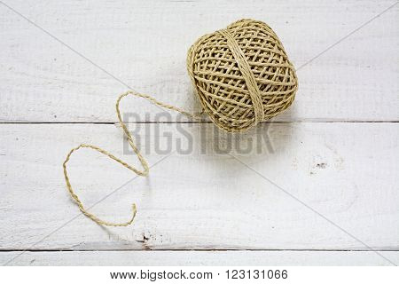 Ball of string with texture and strands on a white painted wooden background copy space