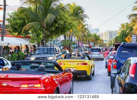 MIAMI BEACH, USA - MAY 9, 2015: The Ocean Drive crowded with cars and people, one is taking a photo out of a convertible.