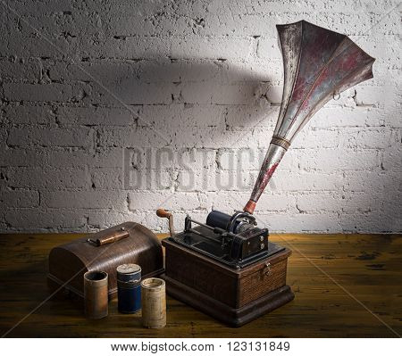 Still life of a phonograph and three cylinder records on a wooden table with white brick wall background