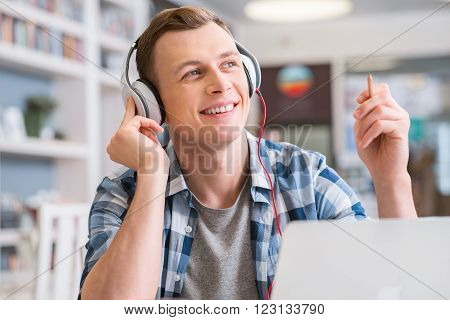 In a good disposition. Delighted positive guy sitting at the table and holding pencil while listening to music poster