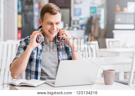 Share your feelings. Cheerful delighted guy sitting at the table and using laptop while wearing headphones