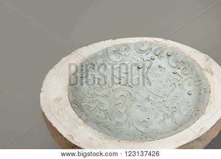 Unbaked decorative plate with ornament in a gypsum form on a grey background