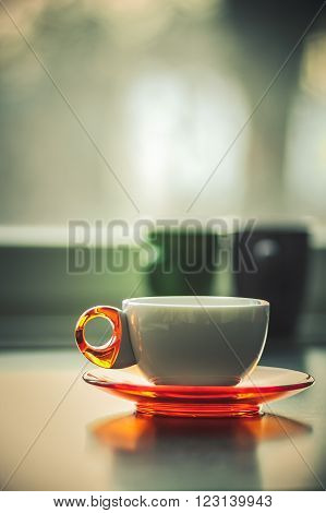 White coffee or tea cup with orange plate in front of a window with purple and green mug in the back in cozy warm orange and pink tranquil purple tones