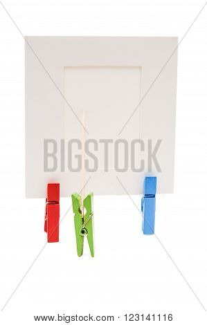 Green clothespin standing in front of a white frame and displays it on a toothpick. The frame holding two colored clothespins