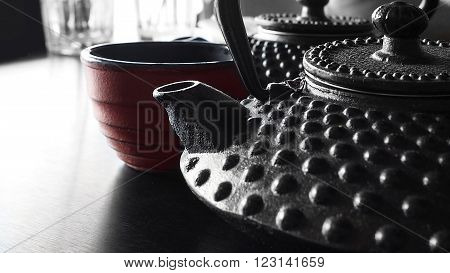 Japanese cast iron tea kettles with tea and japanese tea cup. poster