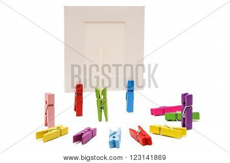 Clothespin is holding a toothpick before the white frame. Other pegs arranged in a semicircle. Two clothespins standing others lying clothespins