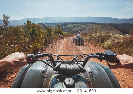 View from a quad bike in nature. Woman in front driving off road on an all terrain vehicle. POV image of a quad biker following another biker on a trail