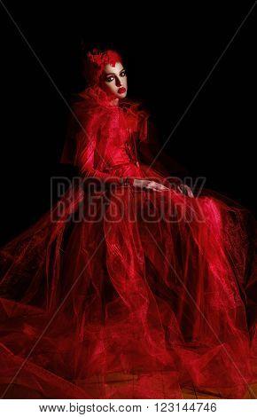 Portrait of a demonic woman in a luxury red dress. Studio shot on a dark background.