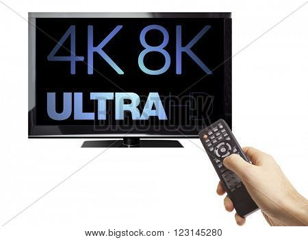 Male hand holding remote control of a TV with 8K 4320p Ultra HD technology logo on