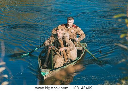 Teryuha, Belarus - October 3, 2015: Two unidentified re-enactors dressed as World War II Soviet russian soldier make crossing of river on a wooden boat