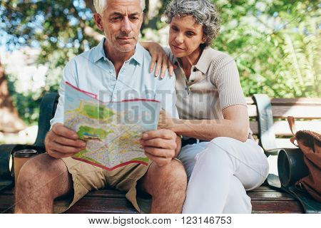 Senior tourist sitting on a park bench reading city map. Man and woman using city guide for finding their location. ** Note: Shallow depth of field