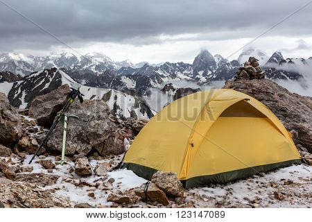 Small Alpine camping Tent located on rocky terrain stone surface and high mountain hills and peaks on background evening sun light