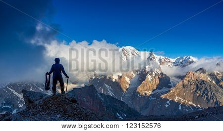 Silhouette Man Staying on Top of Rock Cliff Holding Climbing Gear Stormy Clouds and Peaks Illuminated bright Morning Sun
