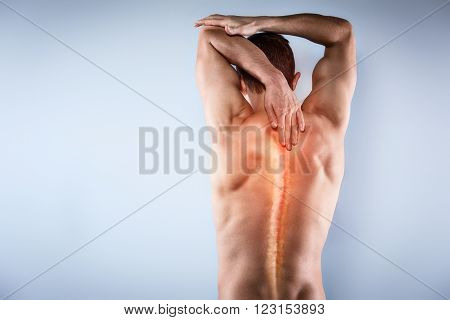 Studio shot of handsome young man with naked torso. Man suffering from neck ache. Red spot on back poster