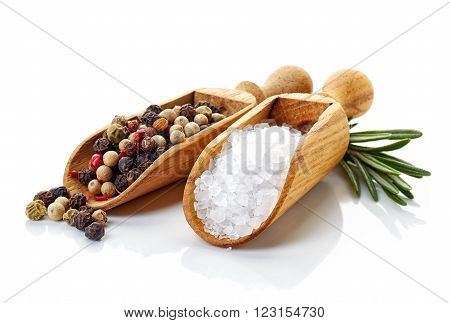 Salt pepper in wooden shovels rosmarinus and isolated on white background