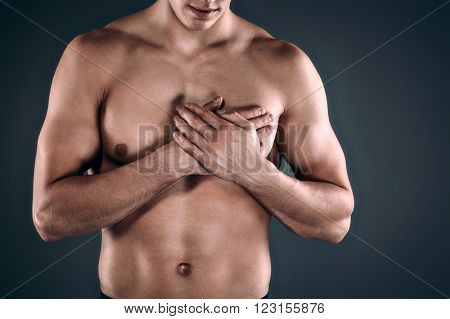 Studio shot of handsome young man with naked torso. Man suffering from heart ache
