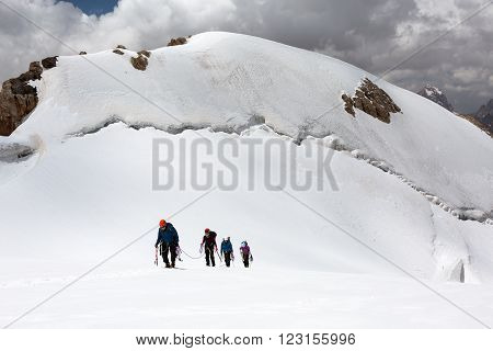 Trekking in Himalaya Hikers Walking Up Glacier in Nepal India Himalaya Way up with Snow Climbing and trekking gear mountain sunny day Majestic Summit background