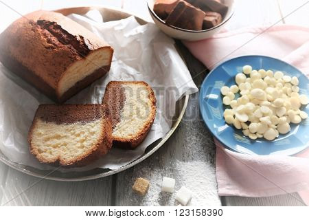 Composition of tasty cake with chocolate morsels and sugar on grey wooden table background