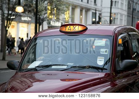 LONDON UK - APRIL 08 2015: London red cab sign turned on at night with evening shop lights in the background