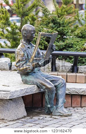 ZAKOPANE POLAND - MARCH 09 2016: Highlander sitting on a rock and reading a newspaper made of bronze figure created to commemorate the 20th anniversary of the magazine Tygodnik Podhalanski