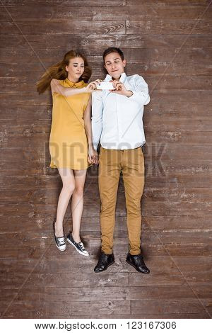 Top view creative photo of beautiful young couple on vintage brown wooden floor. Couple making selfie on mobile phone