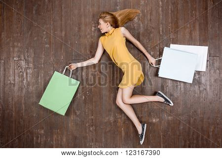 Top view creative photo of beautiful young woman on vintage brown wooden floor. Girl holding shopping bags