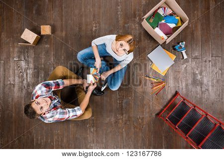 Top view creative photo of beautiful young couple on vintage brown wooden floor. Couple is ready for home renovation